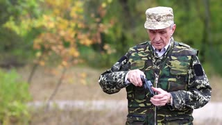 Man in military uniform checks his revolver. Soldier in military uniform inspect his black pistol. Retired officer at shooting range in forest. Man with black gun