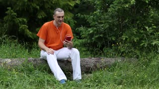 Man in orange t-shirt sits on a fallen tree in the forest and communicates via red smartphone. Adult man sits on a fallen tree in the forest and uses smartphone. Communication through Skype