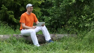 Man in orange t-shirt sits on a fallen tree in the forest and communicates via Tablet PC. Adult man sits on a fallen tree in the forest and uses tablet PC. Communication through Skype