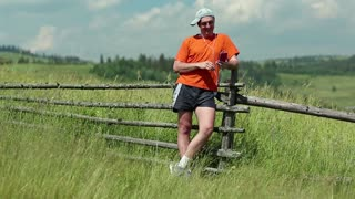 Man in orange t-shirt stands in the field and communicate via smartphone