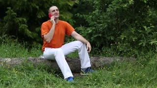 Man in orange t-shirt with a cell phone sits on a fallen tree in the forest. Adult man sits on a fallen tree in the forest and communicates via smartphone