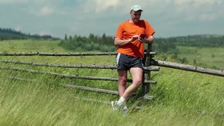 Man in orange t-shirt with a red smartphone stands in the field