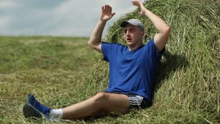Man in T-shirt, boots, cap, shorts  on haystack, stretching, breathing deep. The weather is warm and sunny