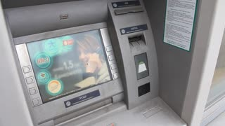 Man inserts the credit card into the ATM (automatic teller machine)