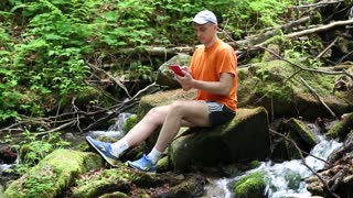 Man is sitting on big moss-grown stone between two small waterfalls. He is making photos of surround nature