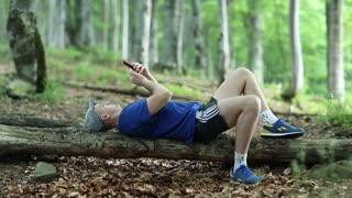 Man lies on a fallen tree in the forest and uses smartphone. Adult man in dark blue t-shirt with red smartphone lies on a fallen tree in the forest. Man lies on a tree