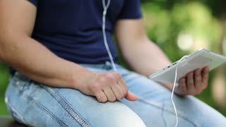Man looks the photos in his tablet computer. Closeup of man hands with white tablet pc and earphones. Man holds in hands white tablet pc. Man looks and flips through the photos in his computer