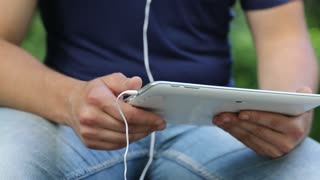 Man looks the photos in his tablet computer. Man holds in hands white tablet pc. Closeup of man hands with white tablet pc and earphones. Man looks and flips through the photos in tablet computer