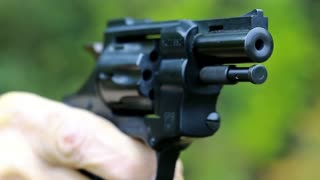 Man shoots a revolver, video with sound. Man cocks and shoots. Soldier shoots a pistol. Man with black gun, raise the cock, cock the gun, close up