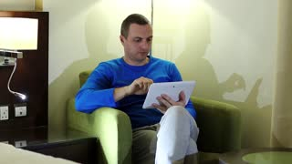 Man sits in armchair in hotel room and uses tablet computer. Young man with tablet pc sits in chair