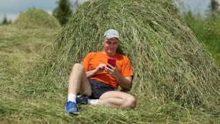 Man sits near haystack and looks through photos on his smartphone. Adult man in orange t-shirt sits near hayrick and holds in hands red smartphone. Male with smartphone. Sportsman with cell phone