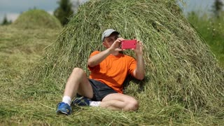 Man sits near haystack and makes photos on his smartphone. Adult man in orange t-shirt sits near hayrick and makes photos on his smartphone for social networks
