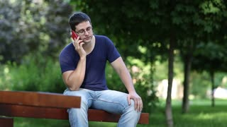 Man sits on the bench in city park and talks on mobile phone. Man communicates via smartphone. Adult man sits on the bench in city park and speaks on smartphone