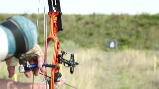 Man training at archery with bow and arrow. Man holds bow in his left hand. Archer shoots a bow at a target