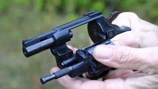 Man turns cylinder of black revolver. Man with black gun, close up. Man holds in hands black revolver with flobert cartridges