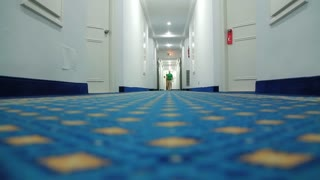 Man walking down a hotel corridor