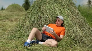 Man wearing orange T-shirt and black shorts lies on haystack, watches tablet, touches display. Weather is sunny and windy