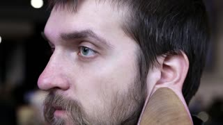 Man with big wooden flesh tunnel in ear