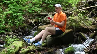 Man with red mobile phone sits on a stone near a small river in forest. Man sits on a stone near a small river and communicates via smartphone
