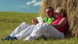 Man with red smartphone and woman with tablet computer sits near a haystack. Mother and son with tablet pc and smartphone looks and flips through the photos in their devices. Male and female, couple