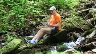 Man with tablet computer sits on a stone near a small river in the forest