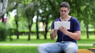 Man with tablet computer sits on the bench in city park. Adult man in blue t-shirt sits on the bench in public garden and uses tablet pc. Man uses white personal computer with earpieces