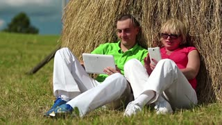 Man with Tablet-PC and woman with smartphone sits near a haystack. Mother and son with tablet computer and smartphone looks and flips through the photos in their devices. Male and female with devices