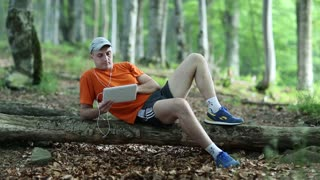 Man with tablet PC lies on a fallen tree in the forest. Man with tablet computer