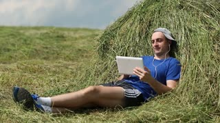 Man with tablet PC sits near a haystack