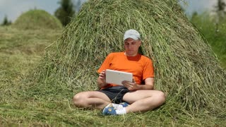 Man with tablet PC sits near haystack. Man in orange t-shirt uses tablet PC. Male with white tablet computer. Sportsman with Tablet PC lies on hayrick