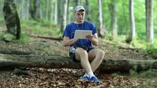 Man with tablet PC sitting on a log in the forest