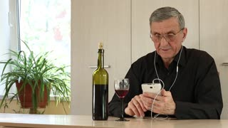 Man with white cell phone sits at a table in office and drinks wine. Senior man in black shirt sits at a table, drinks wine and communicates via smartphone