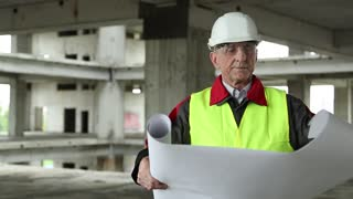 Manager of the works at construction site. Worker in white hard hat with building drawings at project site