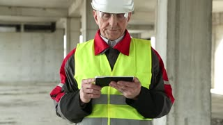 Manager of the works with electronic device at construction site. Master builder in white hard hat with Tablet PC at construction site. Building supervision. Worker in white helmet at project site