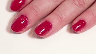 Manicure treatment in beauty salon. Woman applies transparent nail polish over red fingernails