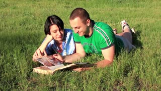 Married couple with photo album lying on the green grass
