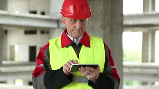 Master builder in red hard hat with tablet PC at construction site. Building supervision. Worker in red helmet at project site