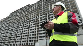 Master builder in white hard hat with tablet PC at construction site. Building supervision. Worker in white hard hat at project site