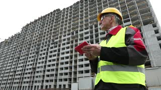 Master builder in yellow hard hat with red smartphone at construction site. Building supervision. Worker in yellow hard hat at project site