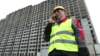 Master builder in yellow hard hat with red smartphone on the construction site. Resident engineer with mobile phone on the construction site. Worker in yellow hard hat on the project site