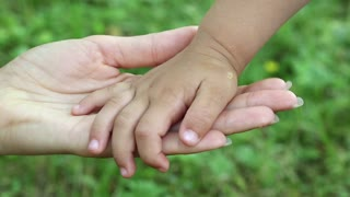 Mother and daughter hands on grass background. Hand in hand. Concern for children