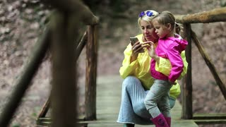 Mother and daughter with smartphone on foot bridge. Family with electronic device on the wooden bridge in the forest. Women in color windcheaters with mobile phone. Baby embrace and kiss his mom