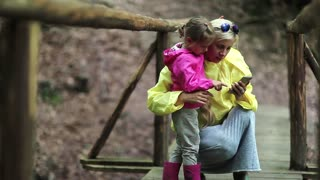 Mother and little daughter looks photos on smartphone. Women in color windcheaters with mobile phone. Family with electronic device on wooden bridge in forest