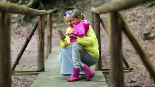 Mother and little daughter with smartphone on foot bridge. Family with electronic device on wooden bridge in forest. Women in color windcheaters with mobile phone. Baby embrace and kiss his mom