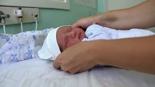Mother and newborn daughter in delivery room