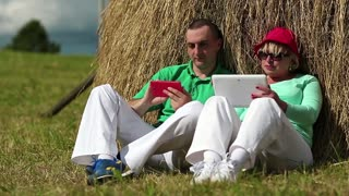 Mother and son in green t-shirts with tablet computer and smartphone looks and flips through the photos in their devices. Man with red smartphone and woman with Tablet-PC sits near a haystack