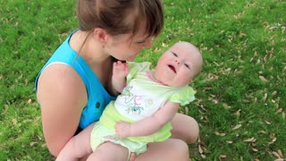 Mother with baby daughter on green grass