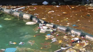 Muddy water. Garbage floats in the sea near the coast. Abuse of environment