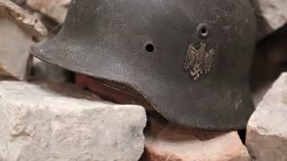 Nazi army helmet of second world war. Iron German army helmet of WW2. German 20th century WWII nazi helmet lies on ruins of a building