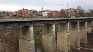 Novoplanovskiy bridge in Kamianets-Podilskyi city, located in historic region of Podolia, western Ukraine. Cars and people on stone bridge above Smotrych river, Kamianets-Podilskyi city, length 136 m